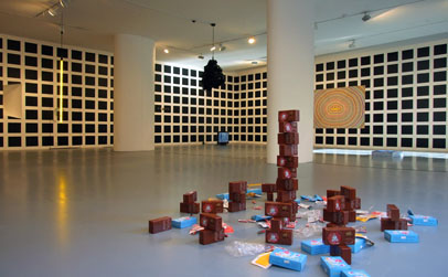 Installation shot, Foreground: Plastic and Batteries and Waste (2010), Buddhist prayer boxes, packaging and batteries accumulated through use